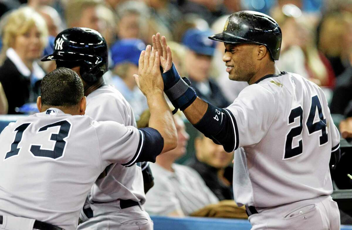 The Yankees' Robinson Cano celebrates with Alex Rodriguez, left, after scoring against the Blue Jays during the eighth inning Wednesday. The Yankees won 4-3.