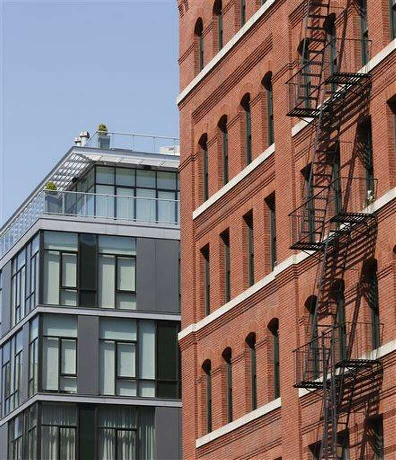 A modern luxury glass apartment building, left, sits across the street from an older red brick apartment, the home of photograher Arne Svenson, Thursday, May 16, 2013 in New York. Residents of a New York luxury apartment building are livid over an exhibition of photos secretly snapped through their apartment windows. (AP Photo/Bebeto Matthews) Photo: AP / AP