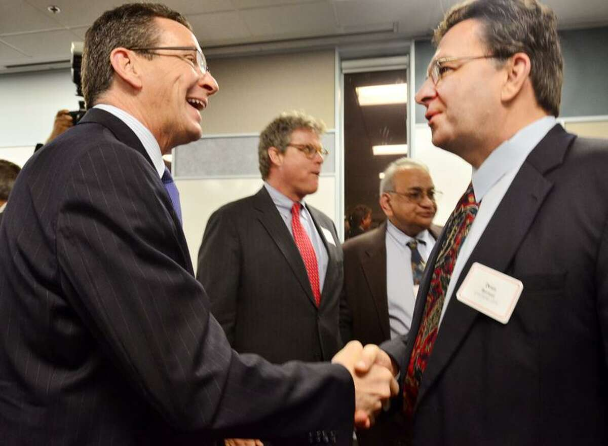 NEW HAVEN--Governor Dannel Malloy laughs as he shakes hands with Dean Bernat, of Colonial LifeInsurance company. Bernat said that he's been told that he and the Governor look alike. Malloy was speaking at a Greater Chamber of Commerce meeting at Assa Abloy.