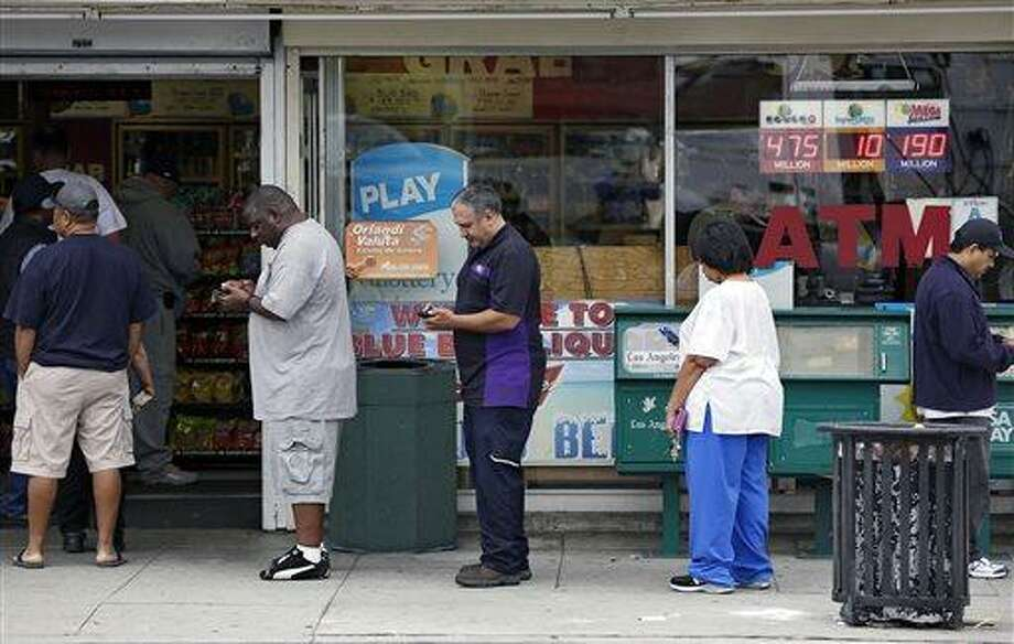 People line up to buy lottery tickets at the Bluebird Liquor store in Hawthorne, Calif. Thursday, May 16, 2013. The multi-state lottery's website said the Powerball drawing jackpot has soared to at least $550 million for next drawing to be held Saturday. (AP Photo/Damian Dovarganes) Photo: AP / AP