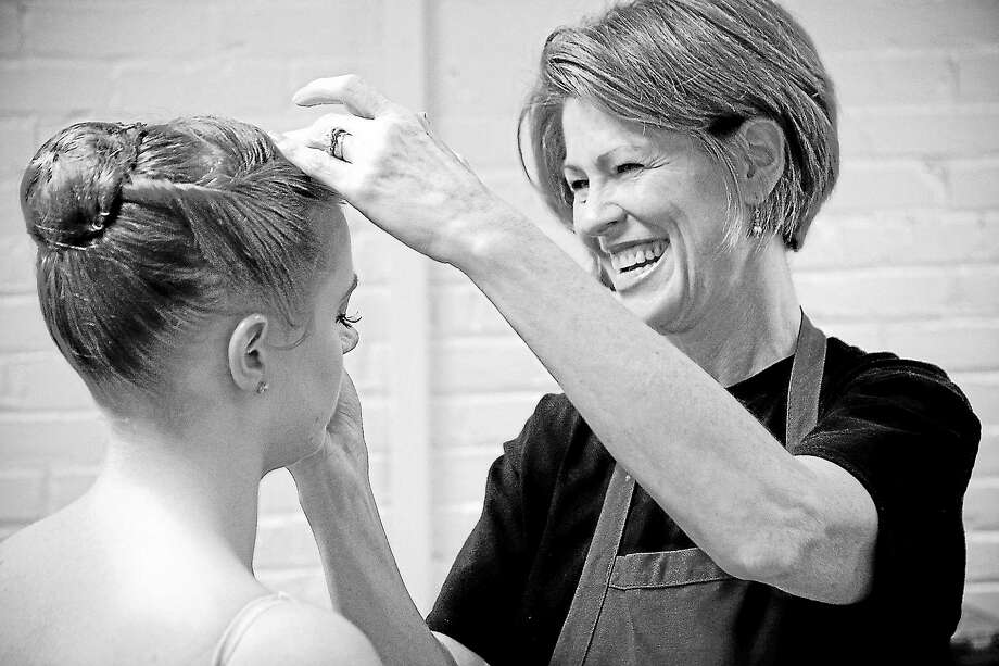 Submitted photo - Nutmeg ConservatoryLisa Snyder, a parent volunteer whose daughter Kendall graduated from Nutmeg Ballet in 2011, helps a dancer prepare for a performance. Photo: Journal Register Co.