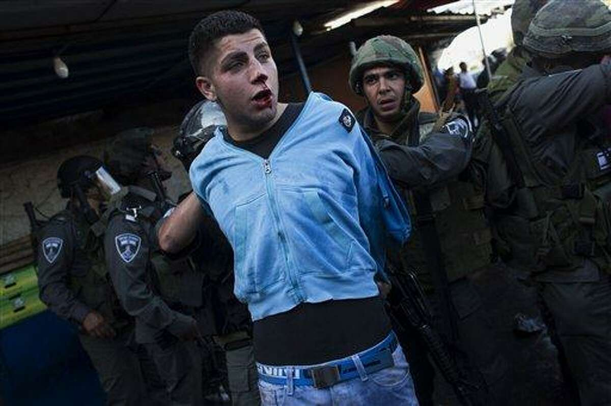 """Israeli security forces detain a Palestinian man during clashes that erupted during a rally marking Nakba Day in Jerusalem, Wednesday, May 15, 2013. Palestinians annually mark the """"nakba,"""" or """"catastrophe"""" -- the term they use to describe their defeat and displacement in the war that followed Israel's founding in 1948. (AP Photo/Bernat Armangue)"""