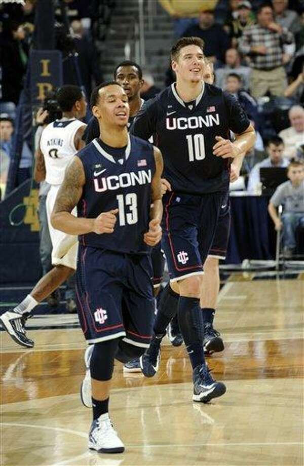 Connecticut players Shabazz Napier, left, and Tyler Olander walk off the court following their 65-58 victory over Notre Dame in an NCAA college basketball game Saturday, Jan. 12, 2013, in South Bend, Ind. Napier scored 19 points and Olander 16 points. (AP Photo/Joe Raymond) Photo: ASSOCIATED PRESS / Joe R. Raymond2013