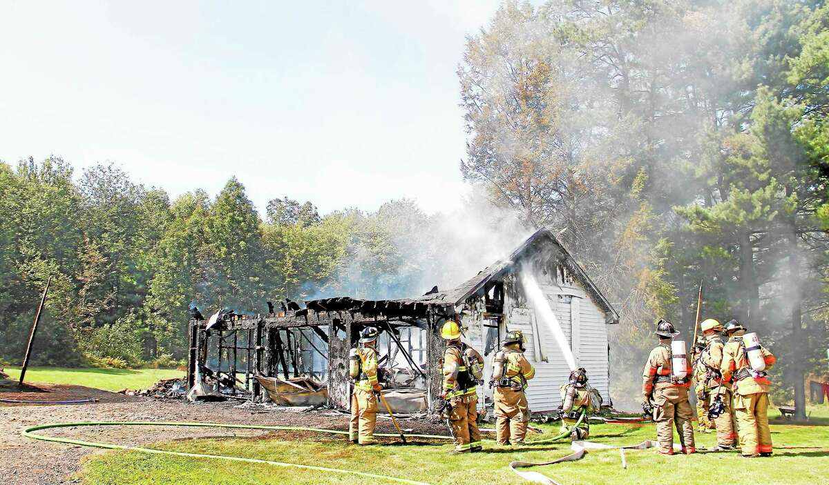 Fire crews work to extinguish lingering flames in a three-unit garage in Litchfield on Tuesday, Sept. 17. The fire destroyed most of the garage and was called a total loss by the Litchfield Fire Marshal.