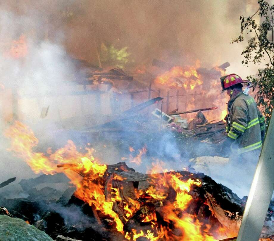 A firefighter walks through the burning rubble of a six-bedroom house on Webbs Hill Road in Stamford, Conn. that exploded on Tuesday, Sept. 17, 2013.  The homeowner was outside near a pool house on the property at the time of the explosion, according to Stamford's director of public safety, Ted Jankowski. (AP Photo/The Stamford Advocate, Lindsay Perry) Photo: AP / The Stamford Advocate