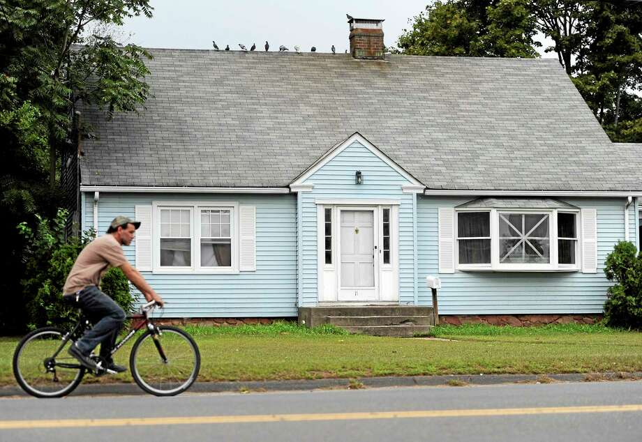 A man rides a bicycle by a house owned by the uncle of former New England Patriot's Aaron Hernandez, Thursday, Sept. 12, 2013 in Bristol, Conn. A group of people who all have ties to a small blue cape-style home in Bristol have become central figures in the investigations linking former New England Patriot Aaron Hernandez to two murder cases. (AP Photo/Jessica Hill) Photo: AP / FR125654 AP