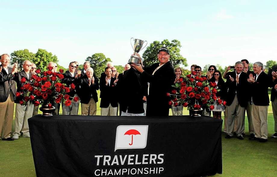 Ken Duke raises the trophy after winning the Travelers Championship in Cromwell this past June. Photo: Fred Beckham — The Associated Press  / FR153656 AP