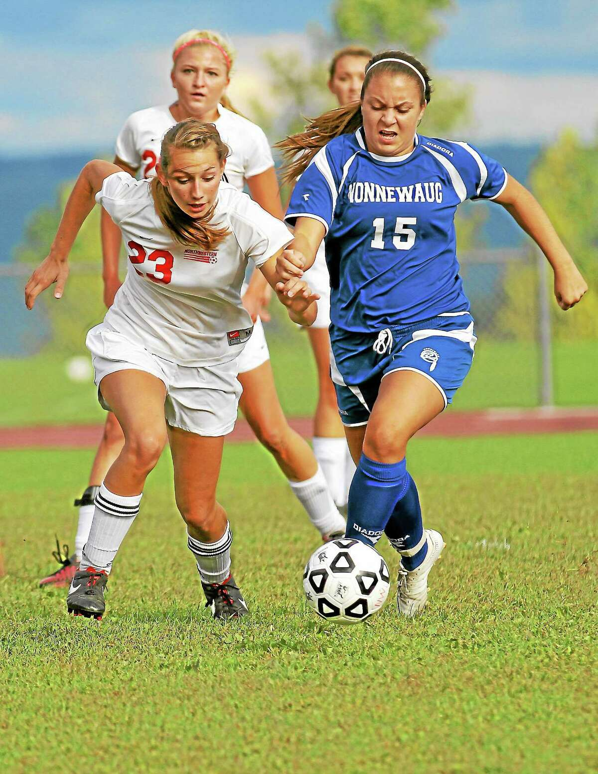 Olivia Mecca (23) and Catherine Flanagan (15) tough it out for control of the ball in Monday afternoon's game at in Winsted.