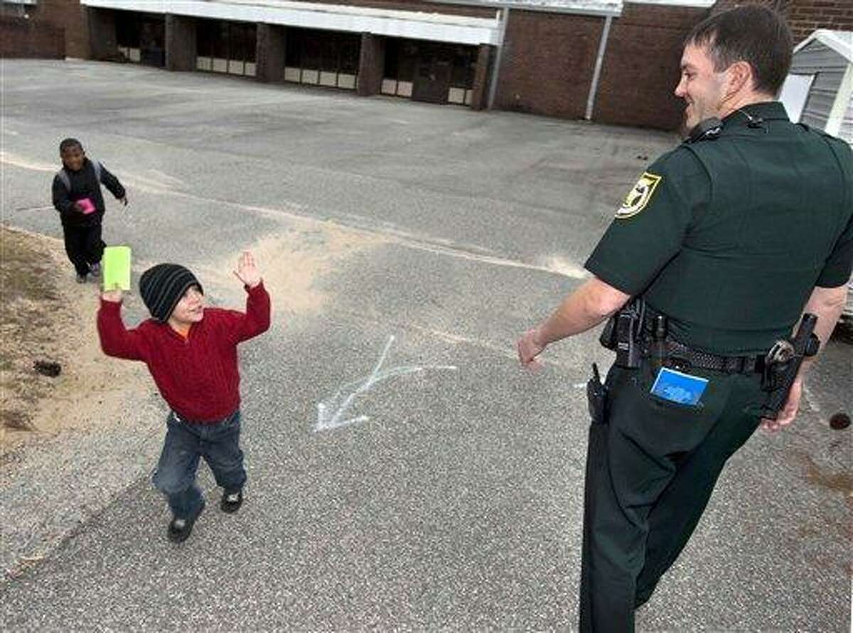 Adam DeCarlo, left, throws up his hands in mock surrender while joking with Deputy Sheriff Jeffrey Moore Tuesday morning at Longwood Elementary School in Shalimar, Fla. The Okaloosa County Sheriff's Office has placed School Resource Officers in all the county's elementary schools in the wake of last month's school shooting in Newtown. In Connecticut, Newtown Schools Superintendent Janet Robinson is urging an indefinite police presence at the district's schools to allay fears among parents and children about gun violence. Associated Press