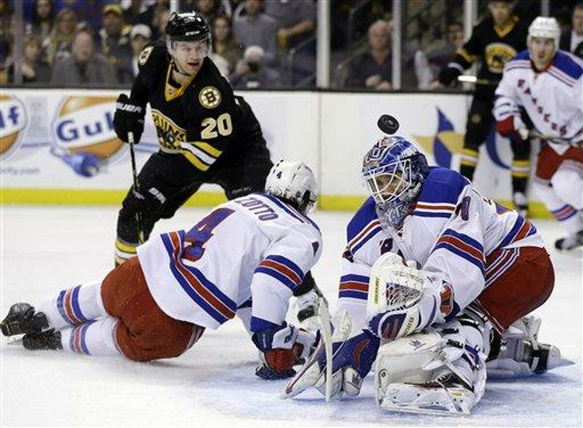 New York Rangers goalie Henrik Lundqvist (30) keeps the puck out of the net as New York Rangers defenseman Michael Del Zotto (4) defends Boston Bruins left wing Daniel Paille (20) during the second period of an NHL hockey game in Boston, Tuesday, Feb. 12, 2013. (AP Photo/Elise Amendola)
