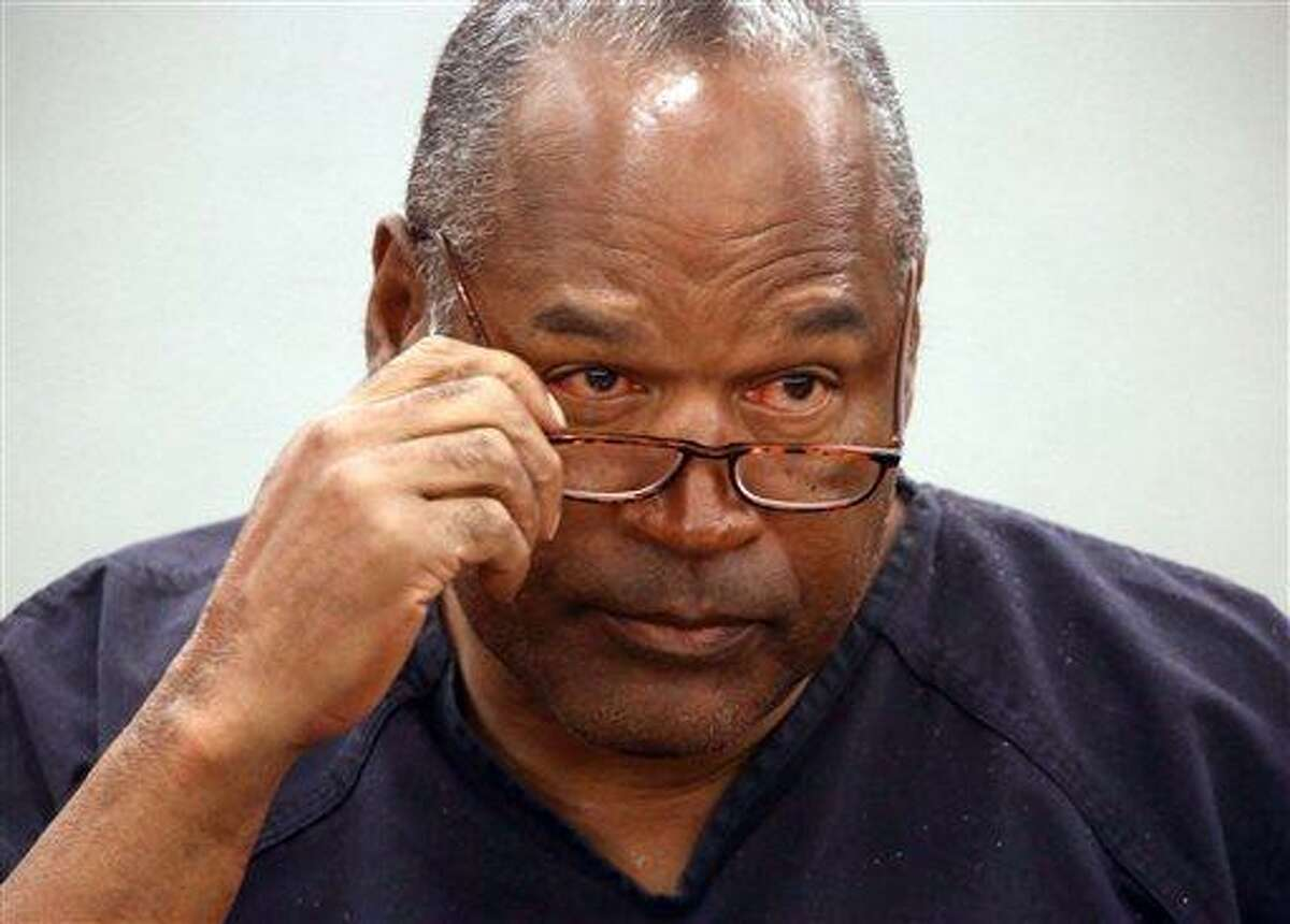 O.J. Simpson removes his glasses as he testifies during an evidentiary hearing in Clark County District Court, Wednesday, May 15, 2013 in Las Vegas. Simpson, who is currently serving a nine to 33-year sentence in state prison as a result of his October 2008 conviction for armed robbery and kidnapping charges, is using a writ of habeas corpus, to seek a new trial, claiming he had such bad representation that his conviction should be reversed. (AP Photo/Las Vegas Review-Journal, Jeff Scheid, Pool)