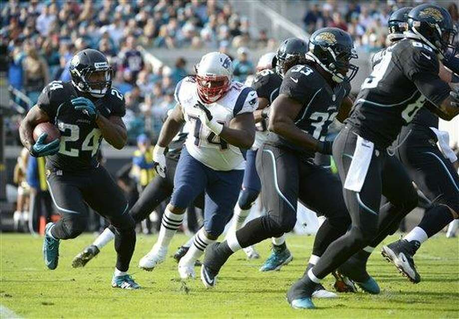 Jacksonville Jaguars fullback Montell Owens (24) runs past New England Patriots defensive tackle Kyle Love (74) behind the blocking of fullback Greg B. Jones (33) and tight end Marcedes Lewis (89) during the second half of an NFL football game in Jacksonville, Fla., Sunday, Dec. 23, 2012.(AP Photo/Phelan M. Ebenhack) Photo: AP / FR121174 AP