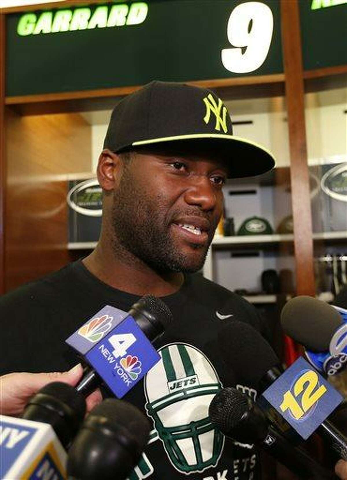 FILE - In this May 2, 2013, file photo, New York Jets quarterback David Garrard talks to reporters during a locker room availability at the team's NFL practice facility in Florham Park, N.J. A person familiar with the decision says Garrard plans to retire because of lingering knee issues, leaving the Jets one fewer quarterback in their open competition. The 35-year-old Garrard was signed in March to provide veteran competition for Mark Sanchez. But Garrard, who hadn't played in a regular-season game in the NFL since 2010 because of injuries, plans to step away because of knee troubles. (AP Photo/Rich Schultz, File)