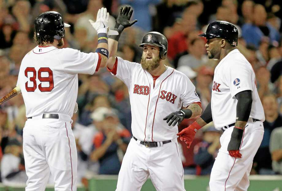 Mike Napoli, center, celebrates with teammates Jarrod Saltalamacchia, left, and David Ortiz, after hitting a two-run home run Sunday. Photo: Steven Senne — The Associated Press  / AP