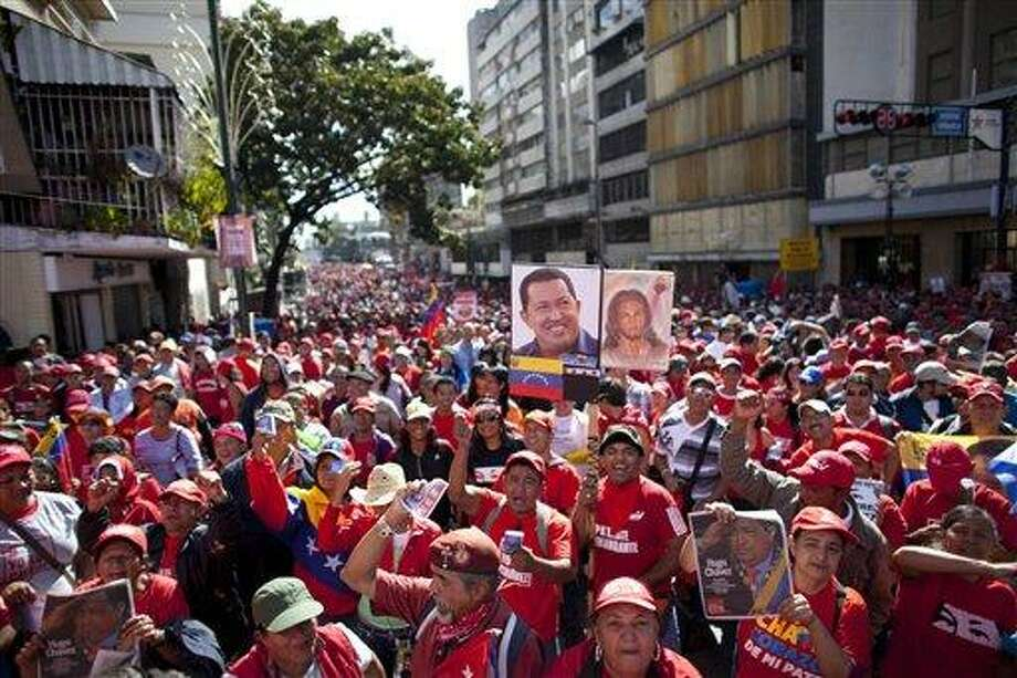 Supporters  of Venezuela's President Hugo Chavez chants slogans during a rally in Caracas, Venezuela, Thursday, Jan. 10, 2013. Hundreds of cheerful supporters rallied outside his presidential palace Thursday in an alternative inauguration for a leader too ill to return home for the real thing. (AP Photo/Ariana Cubillos) Photo: AP / AP