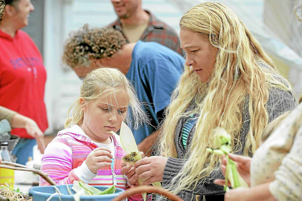 Allison McLauhlin and Jessica Nass make a corncob doll at Barkhamsted Days on the town green in Barkhamsted on Saturday.