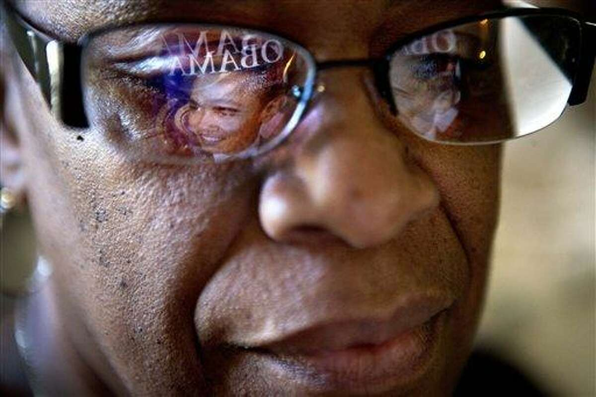 This photo taken Jan. 2, 2013 shows a magazine cover with the image of President Barack Obama reflected in the glasses of Victoria Wimberley, who will be attending President Barack Obama's inauguration for the second time, as she looks over some of the memorabilia in her home in Decatur, Ga. Four years and one re-election after his historic oath-taking as America's first black president, some of the thrill for Barack Obama is gone. Wimberley brought four busloads of people to Washington for the 2009 inauguration. She's coming again this month, though with two fewer buses, which she blamed on the high price for accommodations, not any lack of excitement for Obama. (AP Photo/David Goldman)