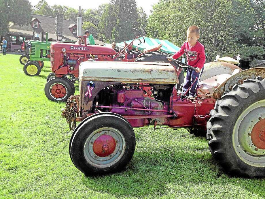 Kids played on a display of antique tractors at the 40th annual New Hartford Day. Photo: Jessica Glenza - Register Citizen