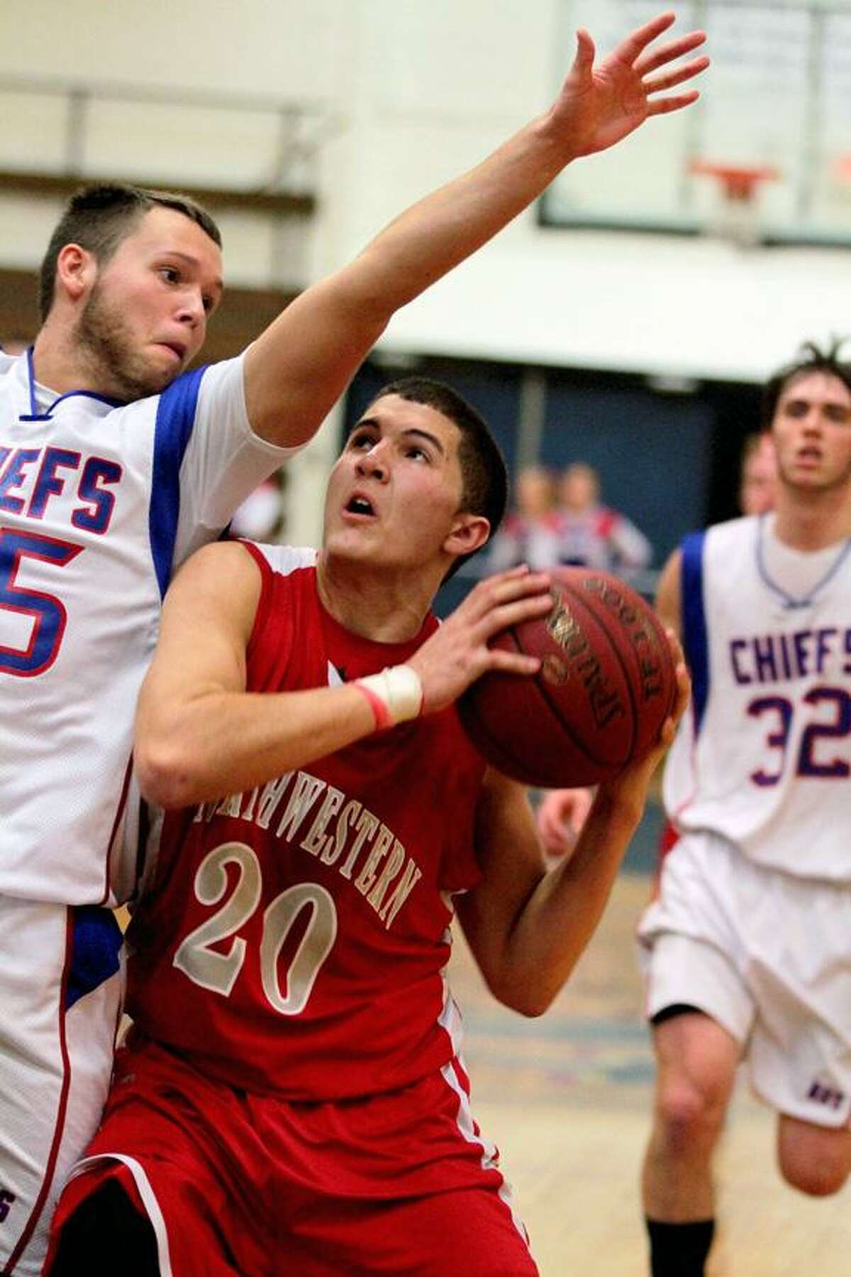 Marianne Killackey/Special to the Register Citizen Northwestern's Connor Guiheen (20) looks to go for a layup as Neil Mendoza (left, 25) of Nonnewaug attempts to block.