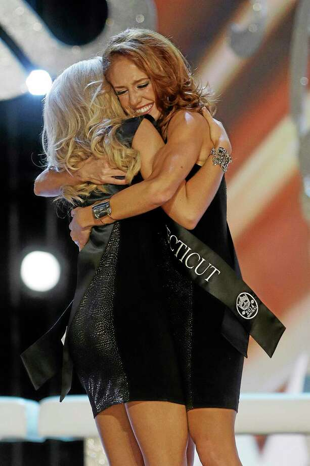 Miss Connecticut Kaitlyn Tarpey, right, hugs Miss Georgia Carly Mathis during the Miss America 2014 pageant, Sunday, Sept. 15, 2013, in Atlantic City, N.J. (AP Photo/Mel Evans) Photo: AP / AP