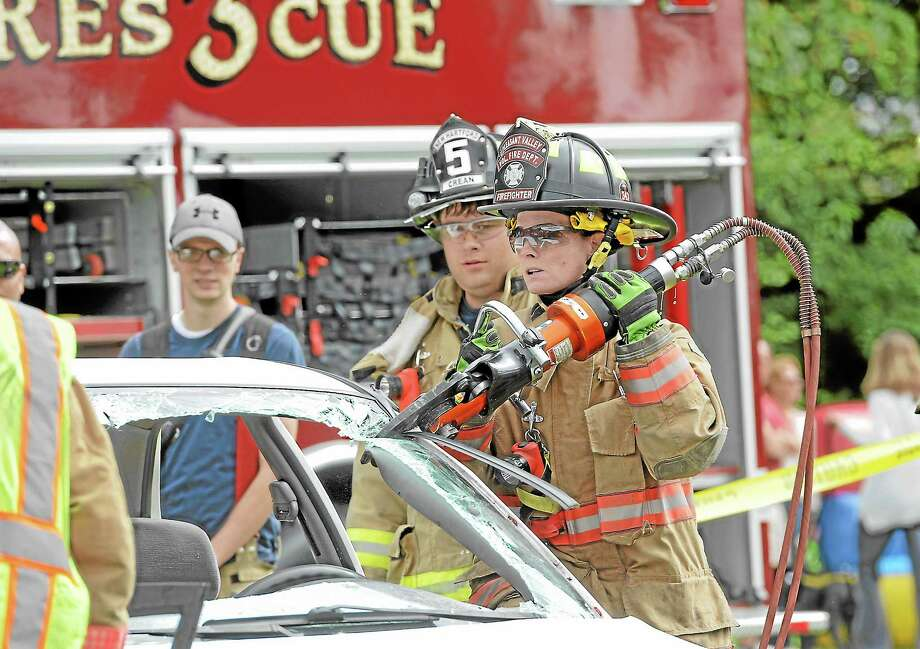 Firefighter Tracey Sikorski of Pleasant Valley FD works to open up a car at the Big Wheels event in New Hartford Saturday afternoon. Photo: Laurie Gaboardi - Register Citizen
