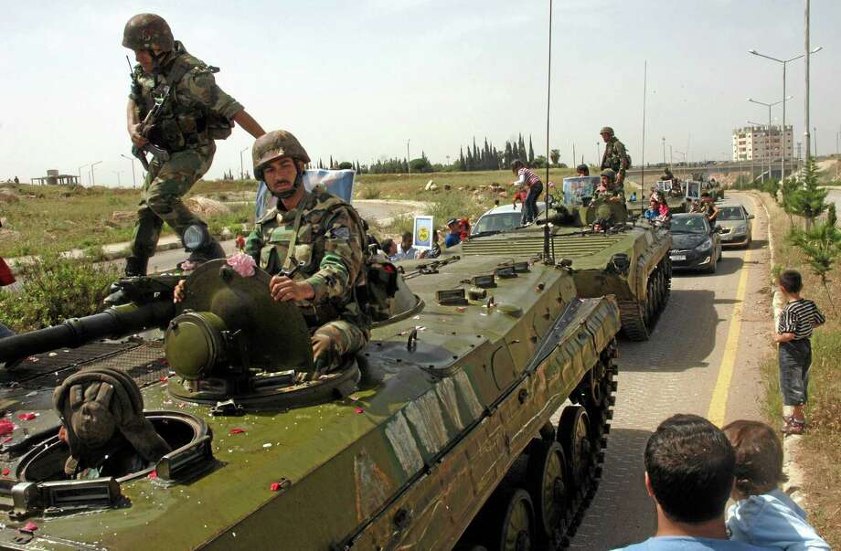In this May 5, 2011, photo released by the Syrian official news agency SANA, Syrian soldiers atop their armored vehicles pull out of the southern city of Daraa, Syria. After two-and-a-half years of civil war, President Barack Obama's larger Syria policy is in disarray even as his administration with help from Russia averted a military showdown for the time-being. The difficulty in understanding what America is trying to do in Syria has persisted in the current debate over how to respond to the Assad government's alleged use of chemical weapons. (AP Photo/SANA) EDITORIAL USE ONLY Photo: AP / SANA
