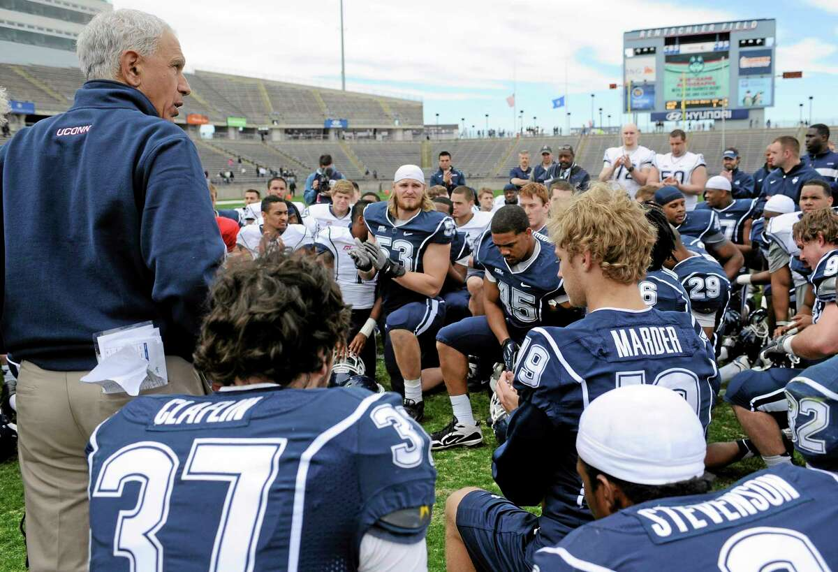Connecticut head coach Paul Pasqualoni, left, talks to his team after UConn's Blue-White spring NCAA college football game at Rentschler Field in East Hartford, Conn., Saturday, April 20, 2013. (AP Photo/Jessica Hill)