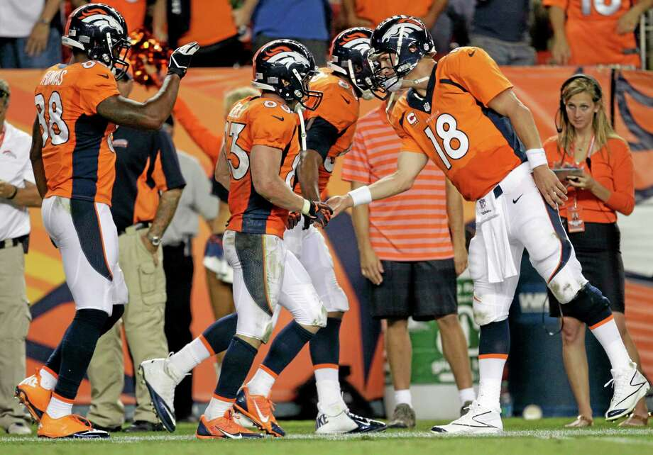 Broncos quarterback Peyton Manning (18) greets teammate Wes Welker (82) after a touchdown pass during the second half of their Sept. 5 game in Denver. Photo: Joe Mahoney — The Associated Press  / FR170458 AP