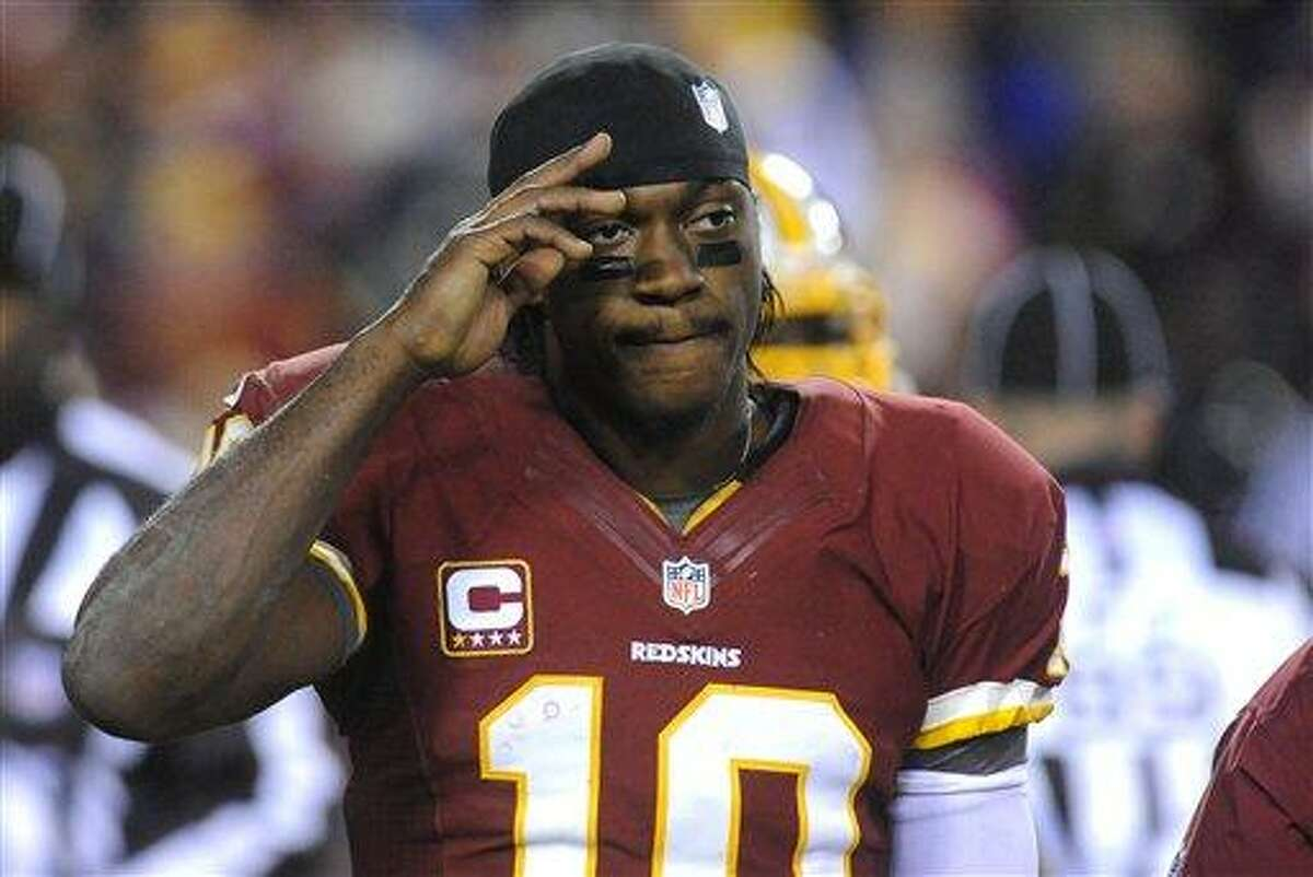 Redskins quarterback Robert Griffin III salutes to the fans as he leaves the field with an injured left leg during the fourth quarter of their NFL playoff football game against the Seahawks, Sunday, Jan. 6, 2012, in Landover, Md. Seattle defeated Washington 24-14. (AP Photo/Richard Lipski)