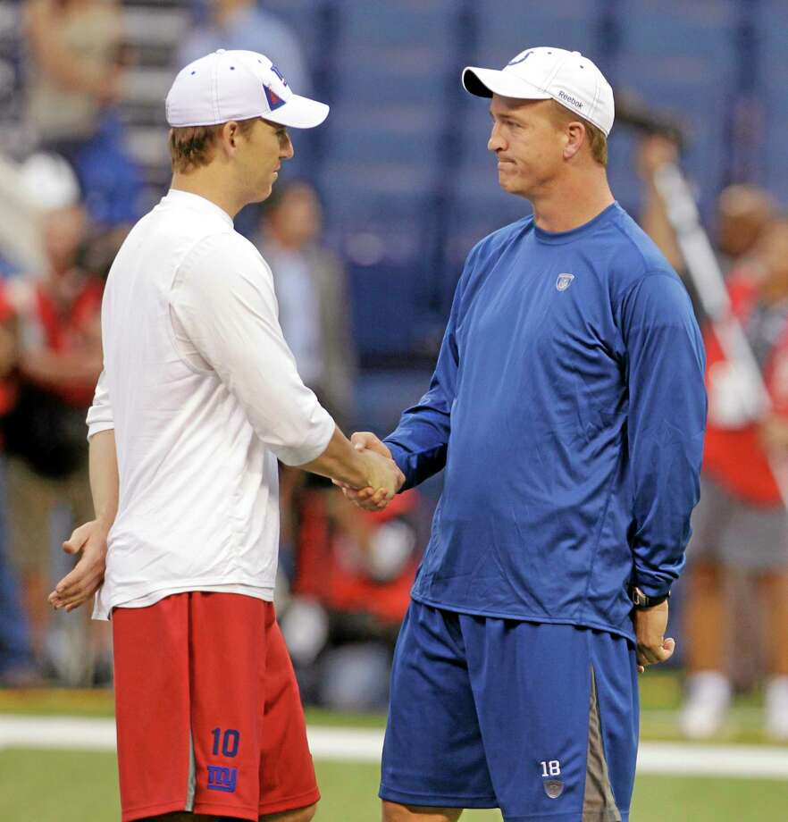 Eli Manning, left, shakes hands with brother Peyton before a 2010 game between the Giants and Colts in Indianapolis. Photo: Darron Cummings — The Associated Press  / AP