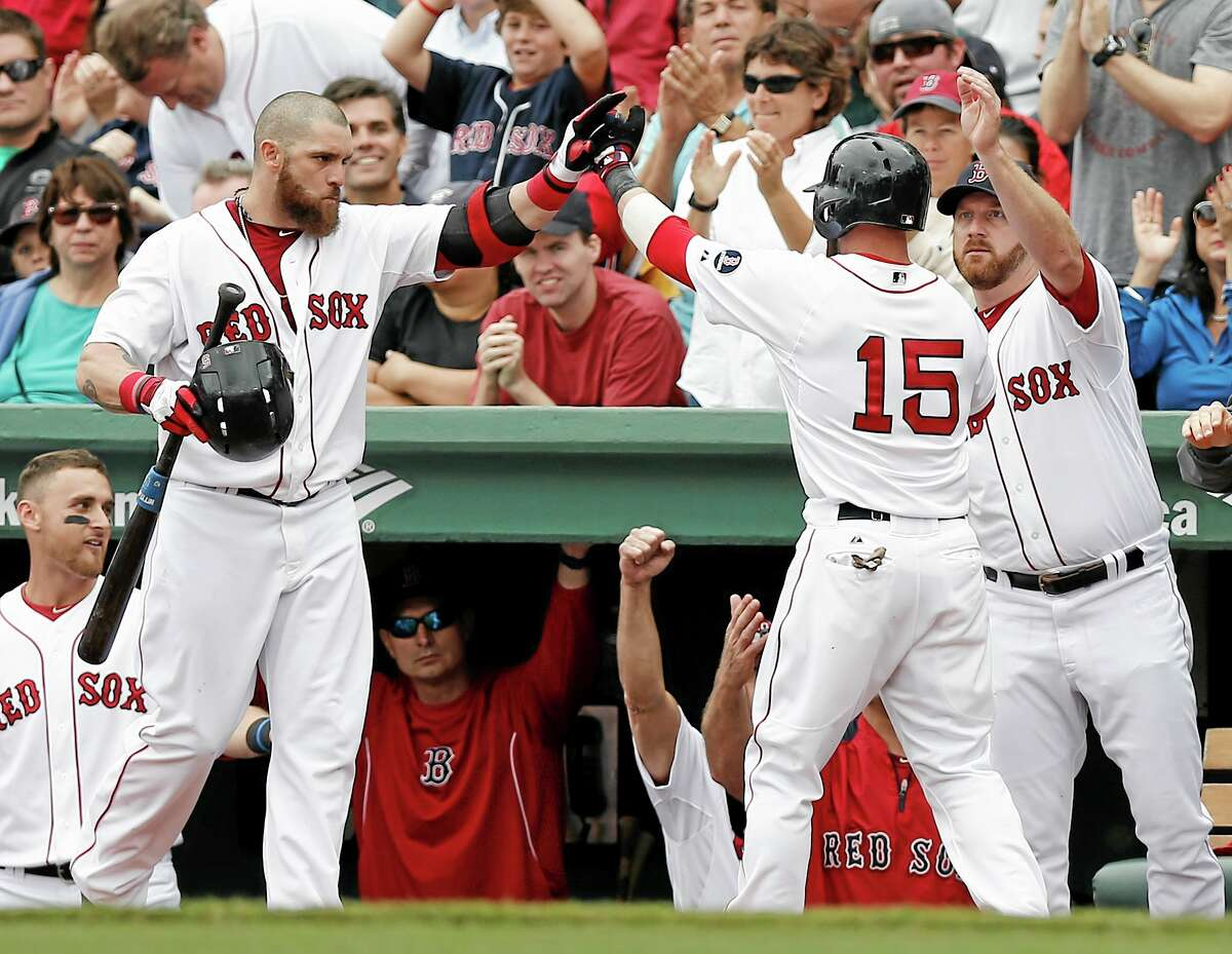 The Red Sox's Dustin Pedroia (15) is congratulated by teammates Jonny Gomes, left, and Ryan Dempster after scoring on a hit by David Ortiz during the third inning of Saturday's win over the New York Yankees at Fenway Park in Boston.