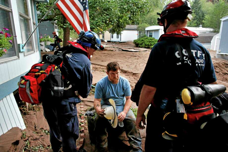 Suffering from dehydration, local resident Fred Rob gets help from emergency responders after floods left homes and infrastructure in a shambles, in Lyons, Colo., Friday Sept. 13, 2013. Days of heavy rains and flash floods which washed out the town's bridges and destroyed the electrical and sanitation infrastructure have left many Lyons residents stranded with minimal access to help, and sectioned off the town into several pieces not reachable one to the other. (AP Photo/Brennan Linsley) Photo: AP / AP