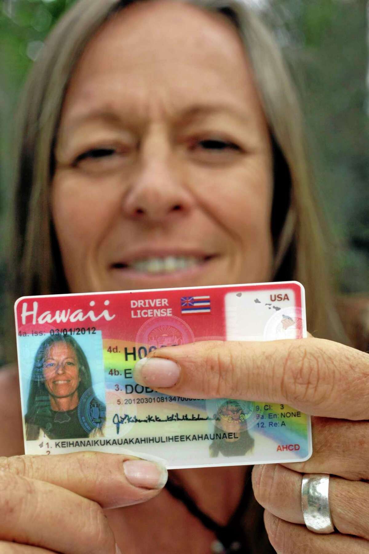 """Janice """"Lokelani"""" Keihanaikukauakahihulihe'ekahaunaele holds her Hawaii drivers license that lacks the space for her full name. Friday, Sept. 13, 2013 in Ocean View, Hawaii. At 36 characters and 19 syllables, the surname is so long that she couldn't get a driver's license with her correct name. (AP Photo/Chris Stewart)"""