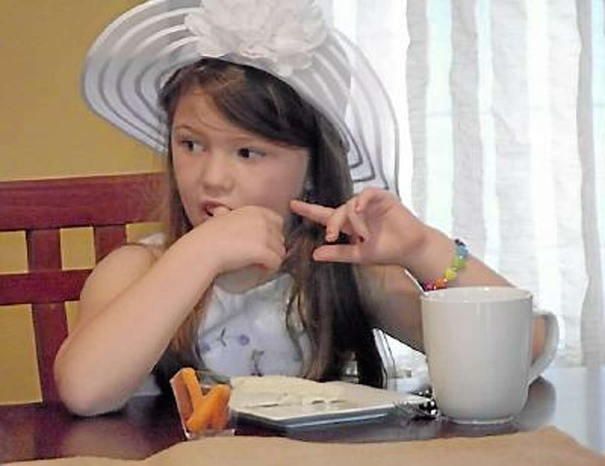 Angelina, a student of Miss Stacey's Early Childhood Education Center enjoys a tea sandwich Tuesday morning at a special tea the students had in recognition of National Etiquette Week. (Jenny Golfin)