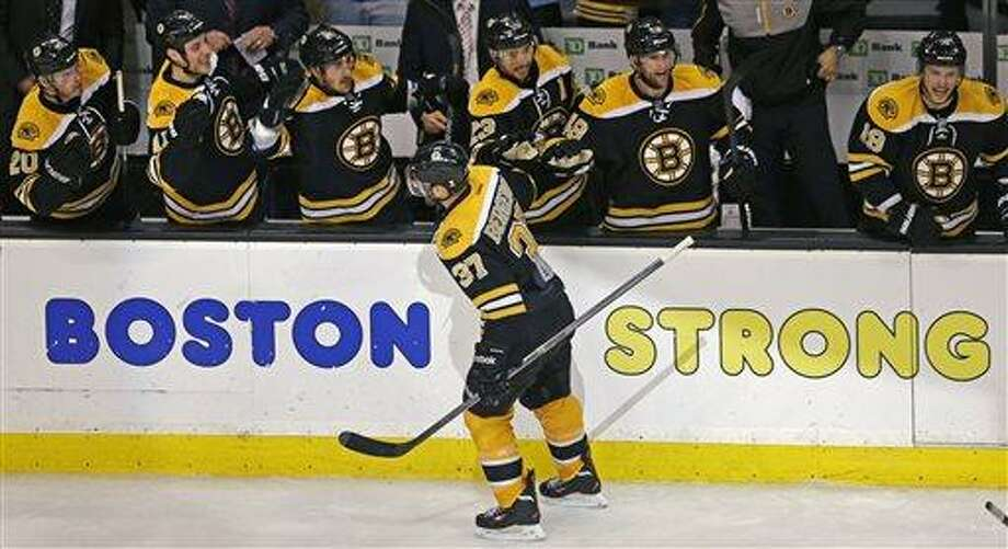 Boston Bruins center Patrice Bergeron (37) is congratulated by teammates after his goal in the final minute of the third period, which tied the game 4-4 forcing overtime against the Toronto Maple Leafs, in Game 7 of their NHL hockey Stanley Cup playoff series in Boston, Monday, May 13, 2013. (AP Photo/Charles Krupa) Photo: AP / AP