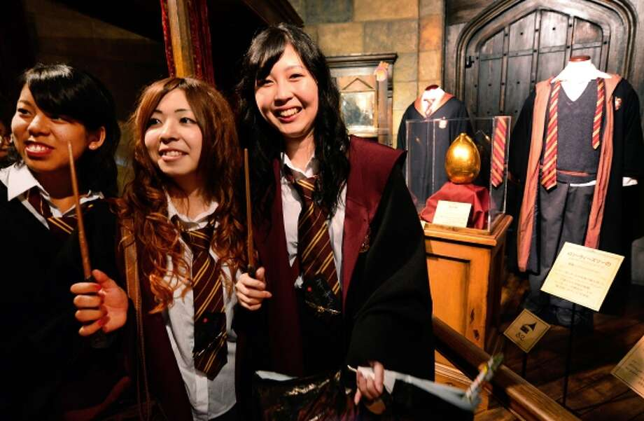 Japanese fans pose in front of Harry Potter costumes during the preview of the Harry Potter exhibition in Tokyo on June 20, 2013. The exhibition will be held from June 22 to September 16.    AFP PHOTO/Toru YAMANAKA        (Photo credit should read TORU YAMANAKA/AFP/Getty Images) Photo: AFP/Getty Images / 2013 AFP