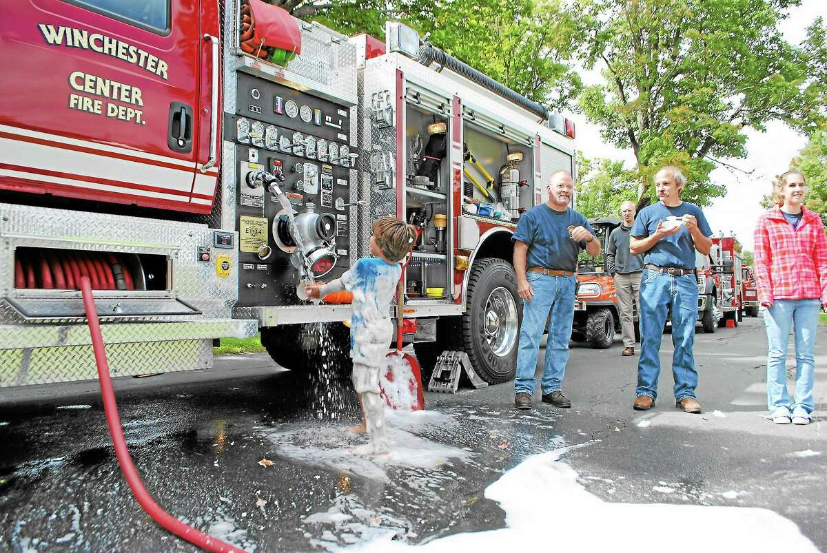 A boy washes off with water from the Winchester Fire Department's engine, at Winchester Center Day, Saturday.