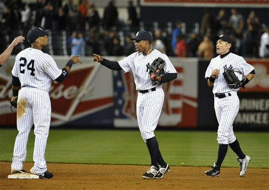 New York Yankees' Curtis Granderson, center, followed by Ichiro Suzuki, celebrates the Yankees' 4-3 win over the Seattle Mariners with Robinson Cano (24) following a baseball game at Yankee Stadium on Tuesday, May 14, 2013, in New York. (AP Photo/Kathy Kmonicek) Photo: AP / FR170189 AP