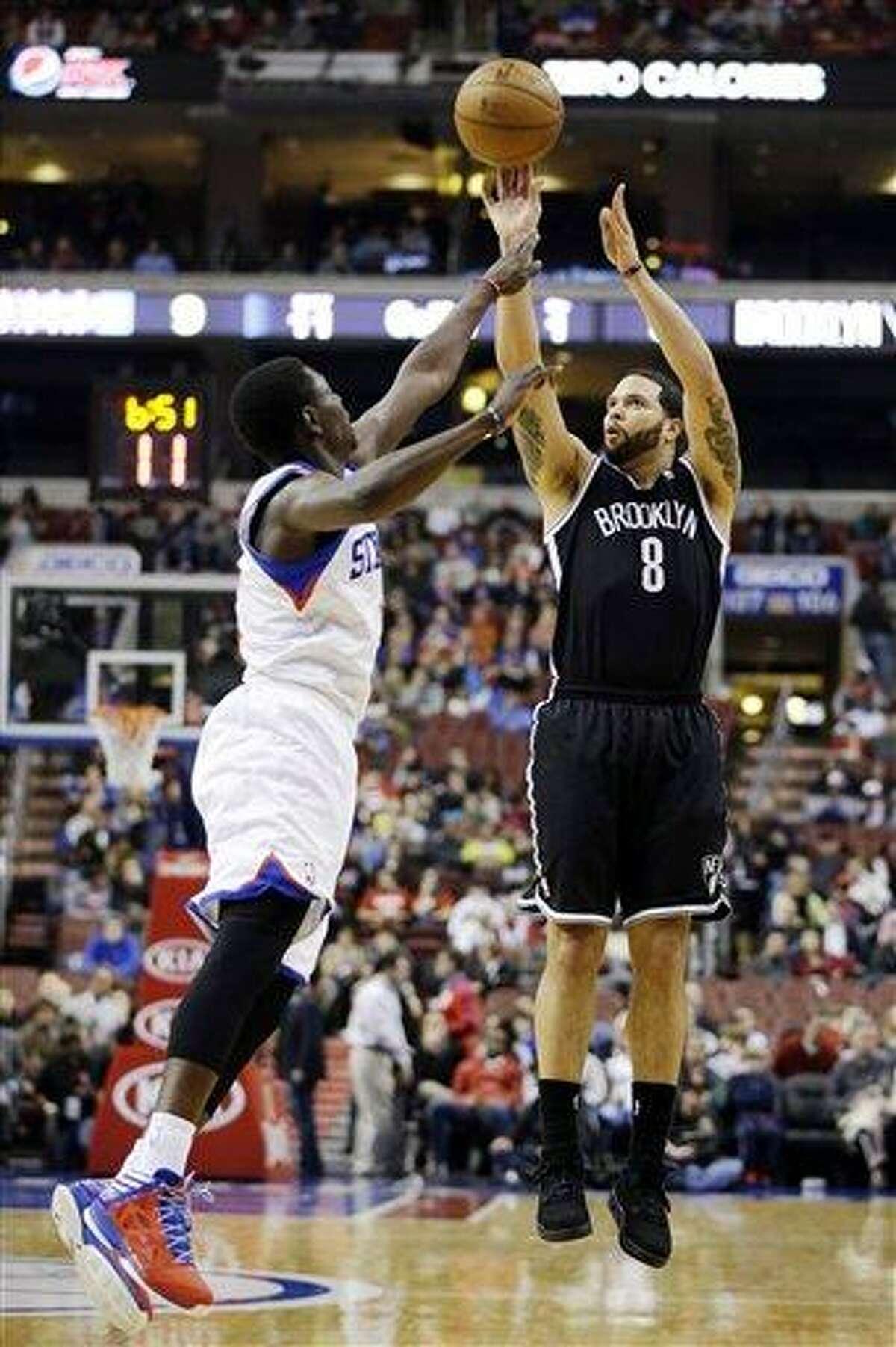 Brooklyn Nets' Deron Williams (8) shoots as Philadelphia 76ers' Jrue Holiday (11) defends in the first half of an NBA basketball game, Tuesday, Jan. 8, 2013, in Philadelphia. Brooklyn won 109-89. (AP Photo/Matt Slocum)