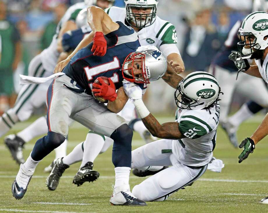 Jets defensive back Ellis Lankster (21) tries to tackle Patriots receiver Julian Edelman during the second quarter Thursday. Photo: Elise Amendola — The Associated Press  / AP