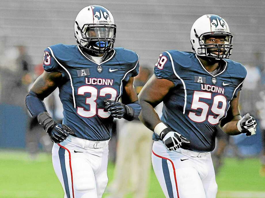 UConn linebacker Yawin Smallwood (33) walks onto the field with defensive tackle Shamar Stephen prior to the Huskies' game against Towson at Rentschler Field on Aug. 29. Photo: Jessica Hill — The Associated Press  / AP2013