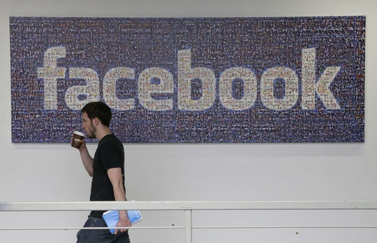FILE - In this March 15, 2013 file photo, a Facebook employee walks past a sign at Facebook headquarters in Menlo Park, Calif. Facebook and Yahoo on Monday, Sept. 9, 2013 asked a secret court to allow them to disclose data on national security orders the companies have received under the Foreign Intelligence Surveillance Act. (AP Photo/Jeff Chiu, File)