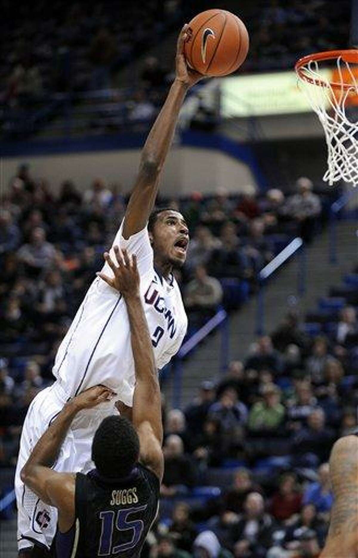Connecticut's DeAndre Daniels, left, drives over Washington's Scott Suggs during the first half of an NCAA college basketball game in Hartford, Conn., Saturday, Dec. 29, 2012. (AP Photo/Fred Beckham)