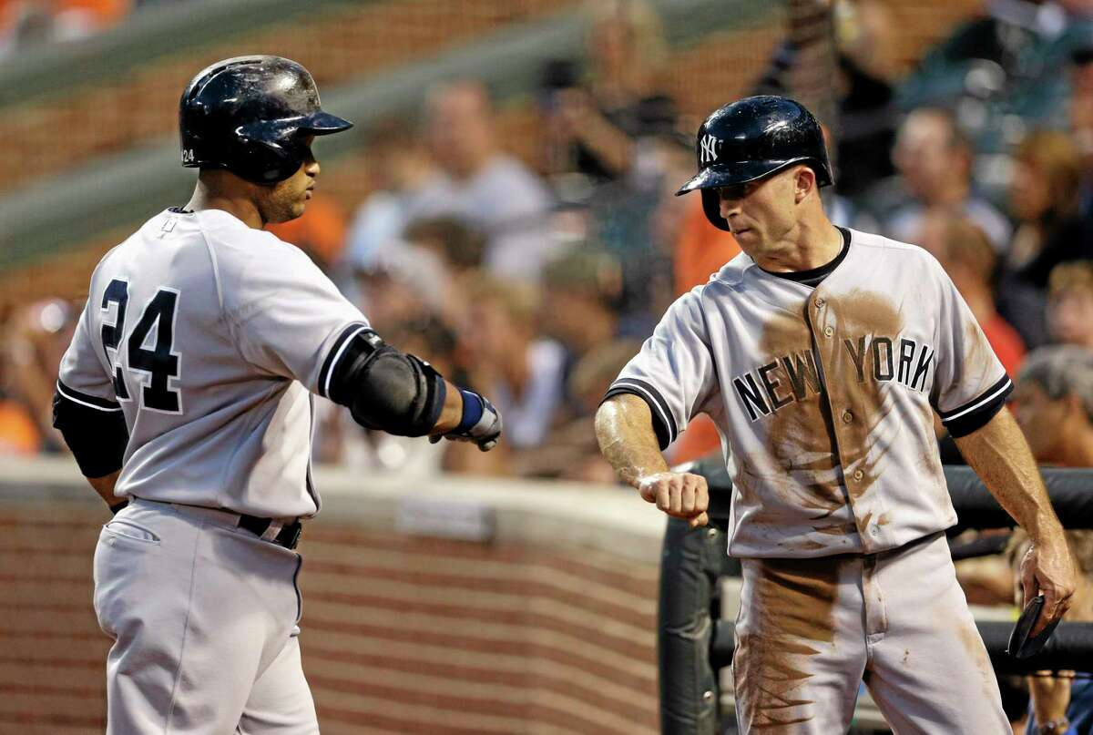The Yankees' Brett Gardner, right, fist-bumps teammate Robinson Cano after he scored a run against the Baltimore Orioles on Cano's groundout Wednesday in Baltimore.