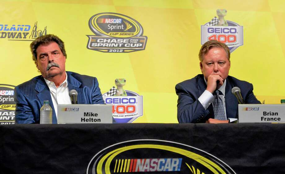 NASCAR Chairman and CEO Brian France, right, and NASCAR President Mike Helton, listen to questions during a press conference during practice for the Sprint Cup Series race at Chicagoland Speedway Friday in Joliet, Ill. NASCAR added driver Jeff Gordon to the Chase championship field, and placed Penske Racing and Front Row on probation. Photo: Nam Y. Huh — The Associated Press  / AP