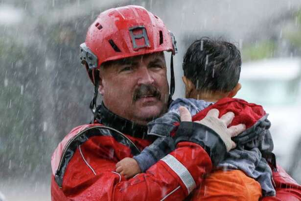 Chad Smith, a Task Force One member from the Dallas Fire Dept., carries Christian Rodriguez, 1, from a rescue boat as people are transferred to a pickup point along Edgebrook Sunday, August 27, 2017.