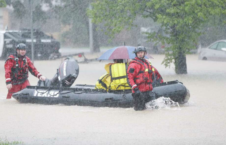 Rescuers pull a boat to take people to be transferred at a pickup point along Edgebrook Sunday, August 27, 2017. Photo: Melissa Phillip / Houston Chronicle 2017