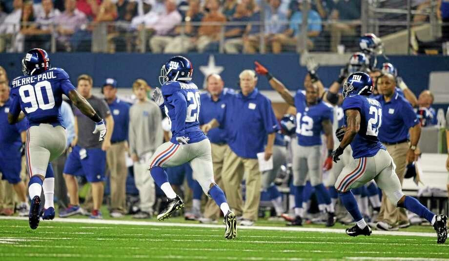 The Giants' Jason Pierre-Paul (90) and Prince Amukamara (20) lead the way as safety Ryan Mundy (21) runs back an interception against the Dallas Cowboys on Sunday in Arlington, Texas. Photo: Tony Gutierrez — The Associated Press  / AP