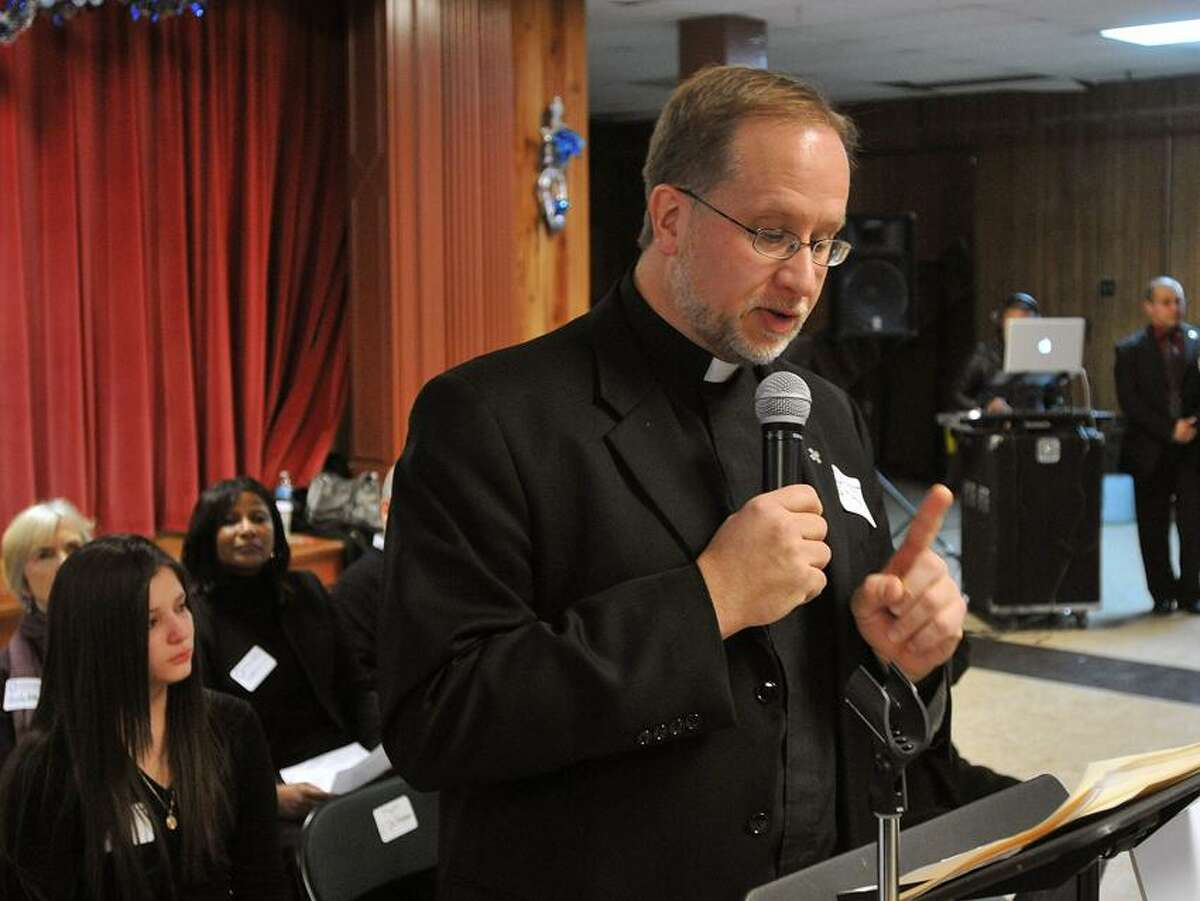 The Rev. James Manship speaks to the crowd at the St. Rose's of Lima church supporting a driver's license program for undocumented immigrants in CT. Peter Casolino