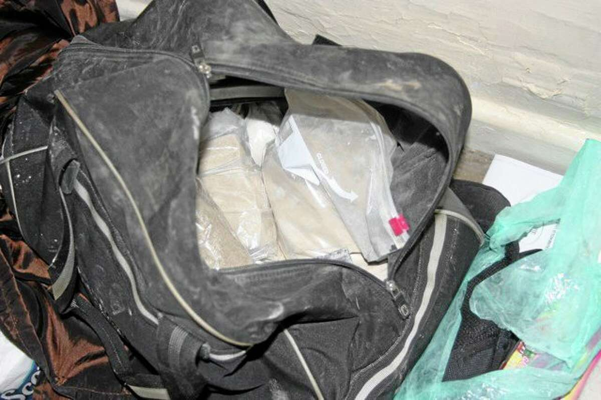 In this photo provided by the U.S. Drug Enforcement Administration, bags of heroin are seen inside an unzipped bag on a closet floor Wednesday, June 12, 2103, at an apartment in the Bronx borough of New York. Authorities executing a warrant seized over 24 pounds of heroin as well as equipment used in its processing for distribution. Three men were arrested and charged with Criminal Possession of a Controlled Substance in the First Degree. (AP Photo/U.S. Drug Enforcement Administration)